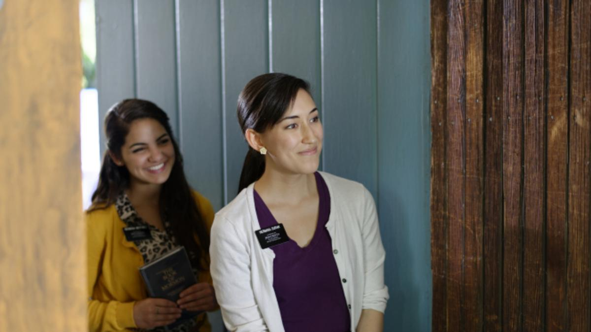Two sister missionaries standing and smiling at an open door