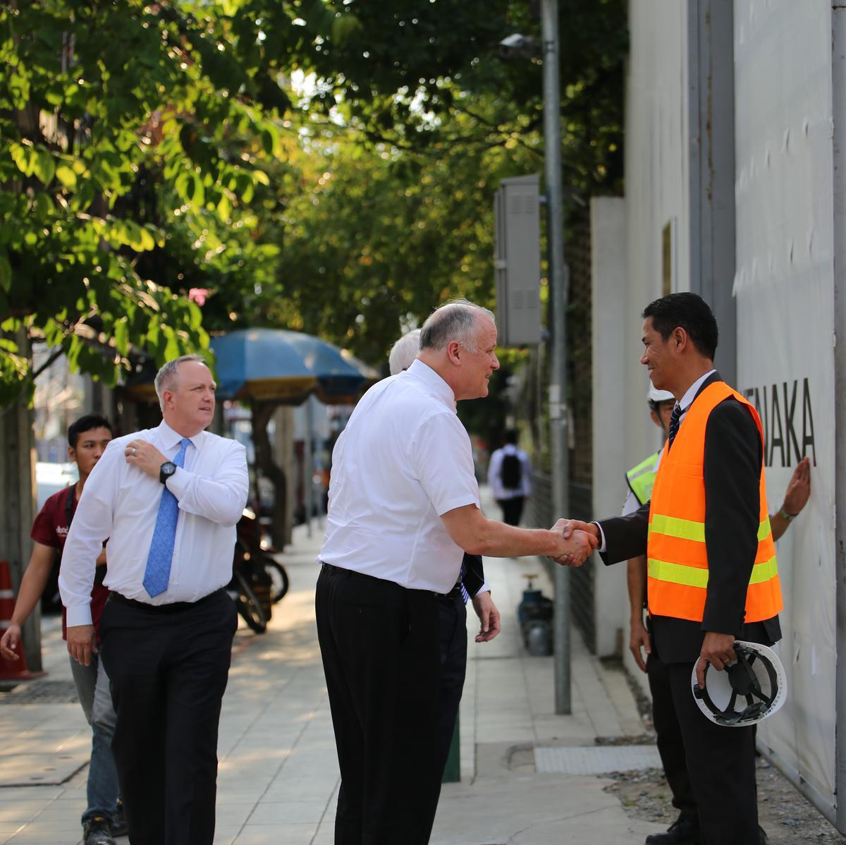 เอ็ลเดอร์โฮเมอร์ทักทายเจ้าหน้าที่รักษาความปลอดภัยที่ถนนเพชรบุรีตัดใหม่หน้าสถานที่ก่อนสร้างพระวิหาร