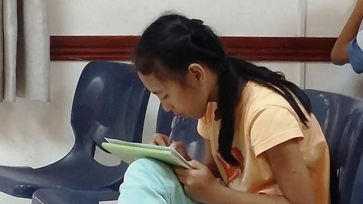 Một em thiếu nữ chăm chú học hỏi trong buổi Đại Hội. Hình bởi Deborah Coffey.