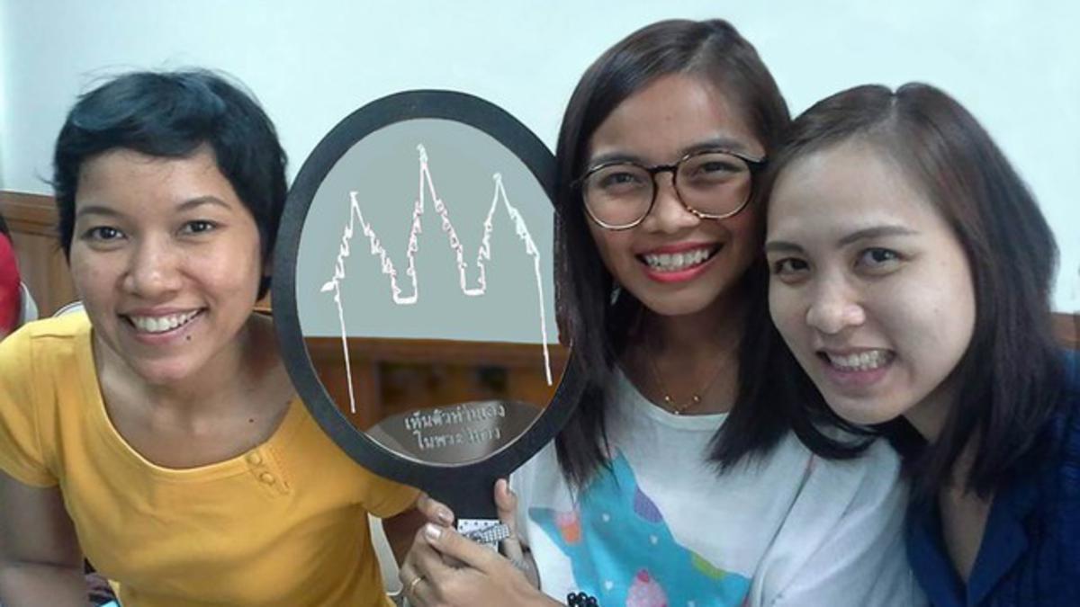 mujeres jovenes con un espejo que tiene la imagen del templo