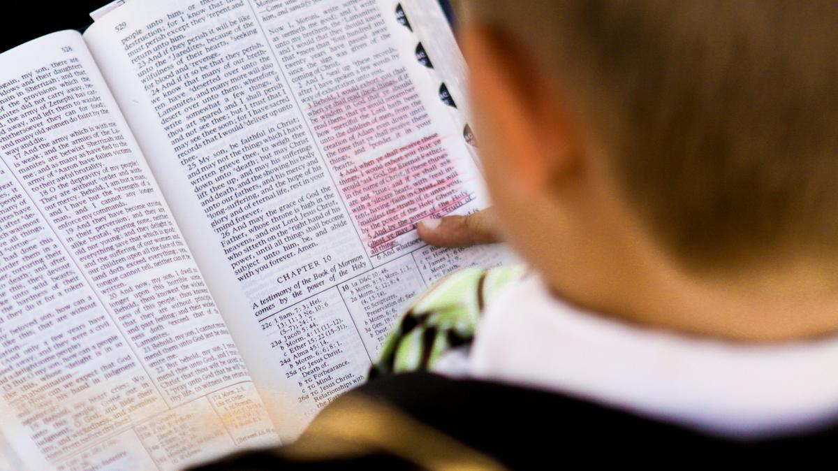 Niño lee las escrituras en el libro de Moroni