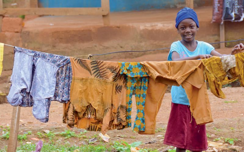 Una niño colgando la ropa para secarse.
