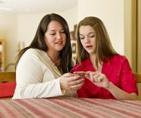 Δύο γυναίκες που μοιράζονται το κινητό τους