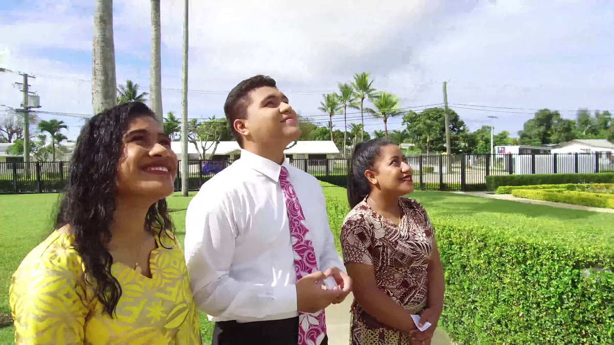 Two young women and one young men in Tonga looking at the Temple