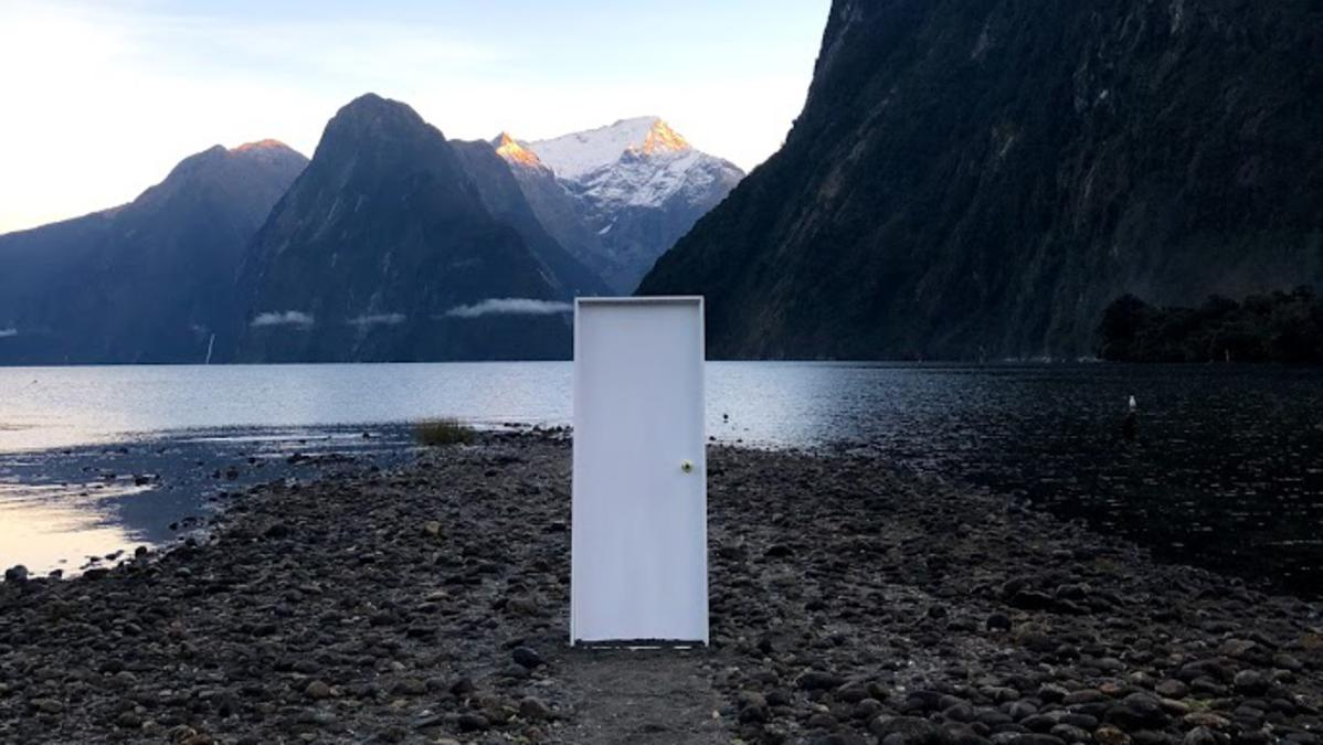 Door on rocky ground near a mountain. There is a small body of water nearby.