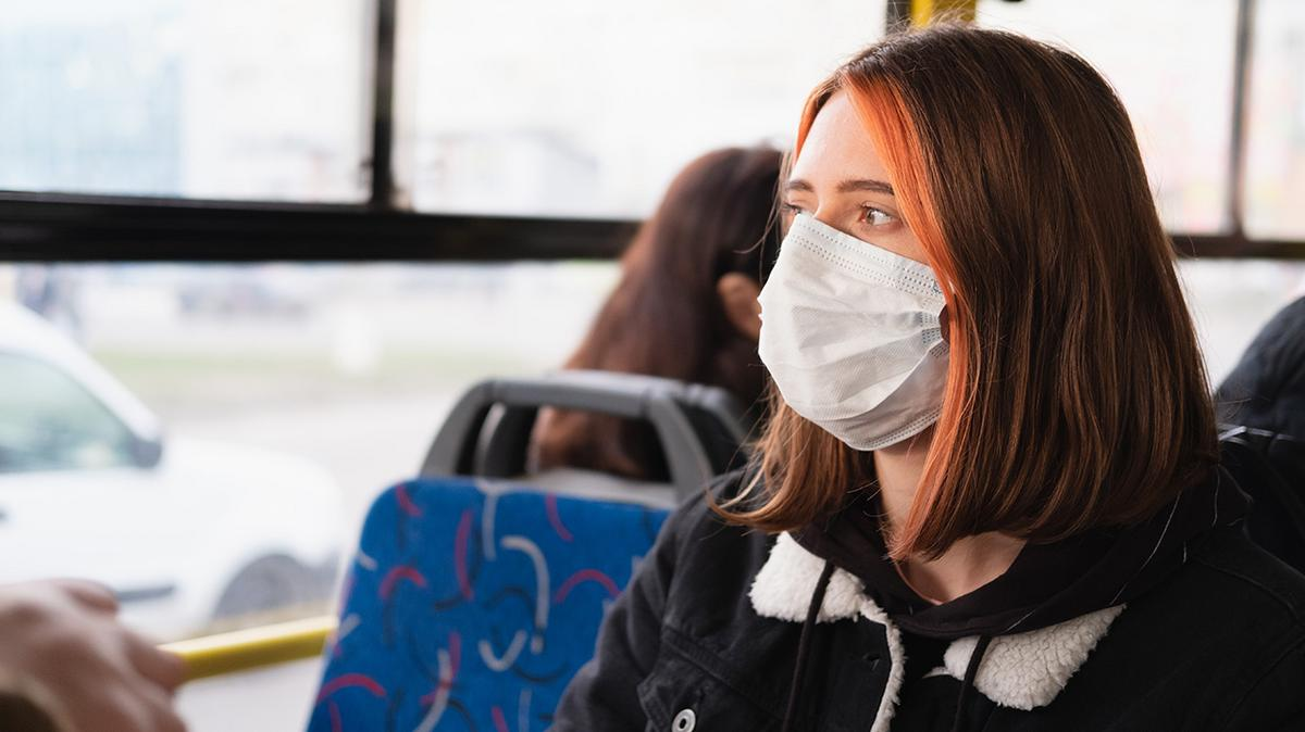 Girl on bus wearing mask