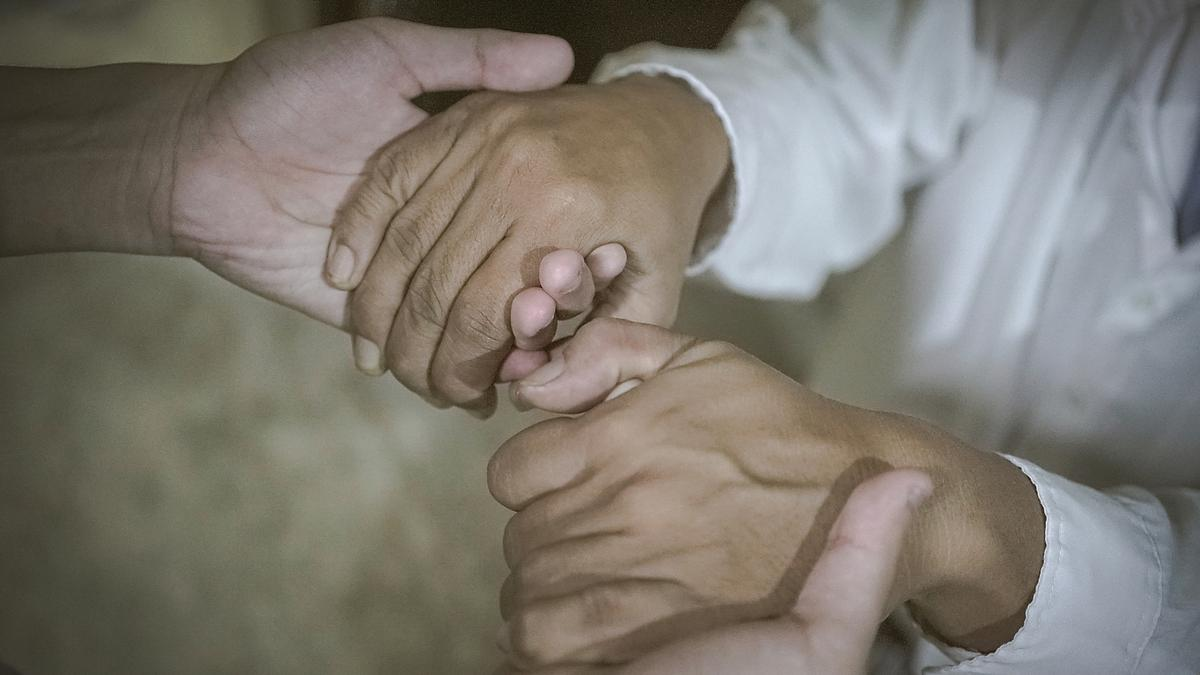 Two people holding hands, supporting each other.