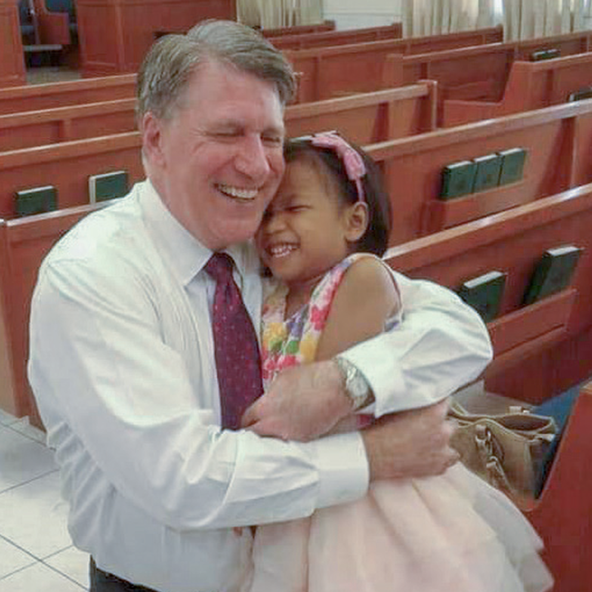 Elder Schmutz hugging a child in the Philippines.