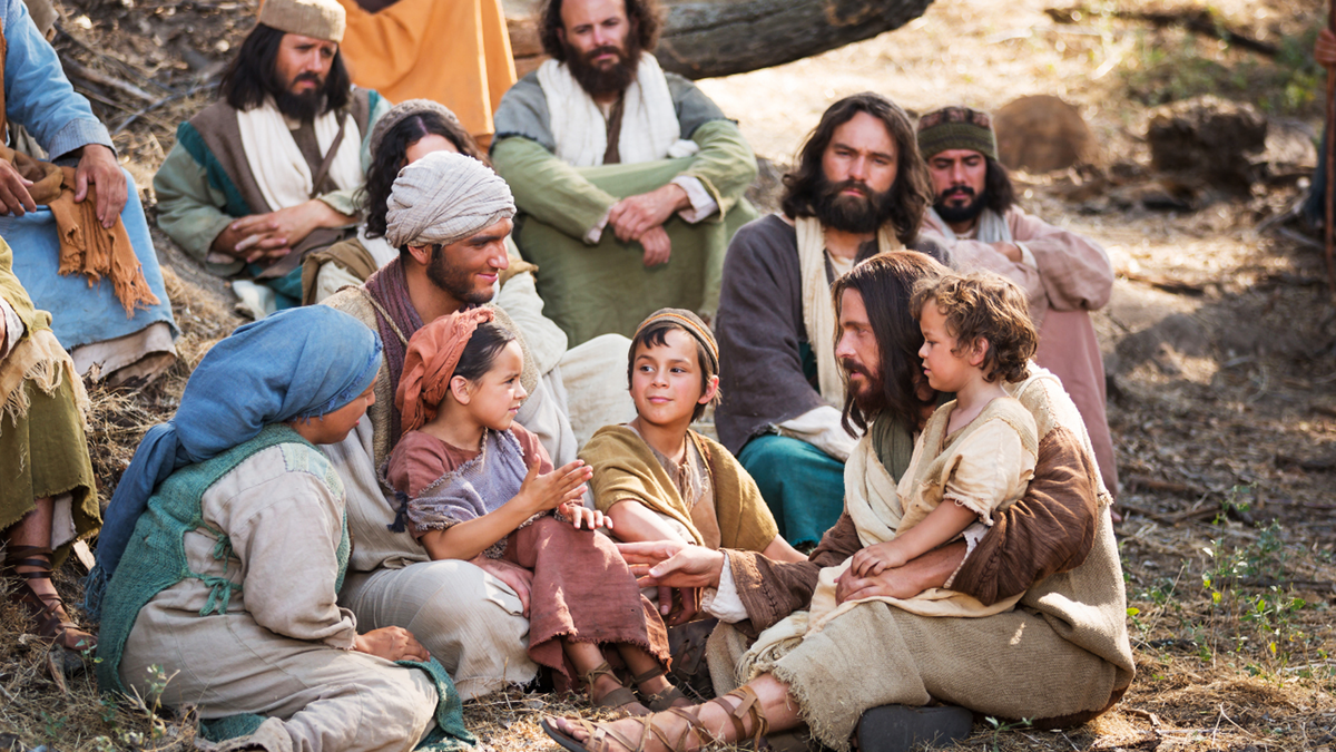 Jesus Christ teaches a family with young children.