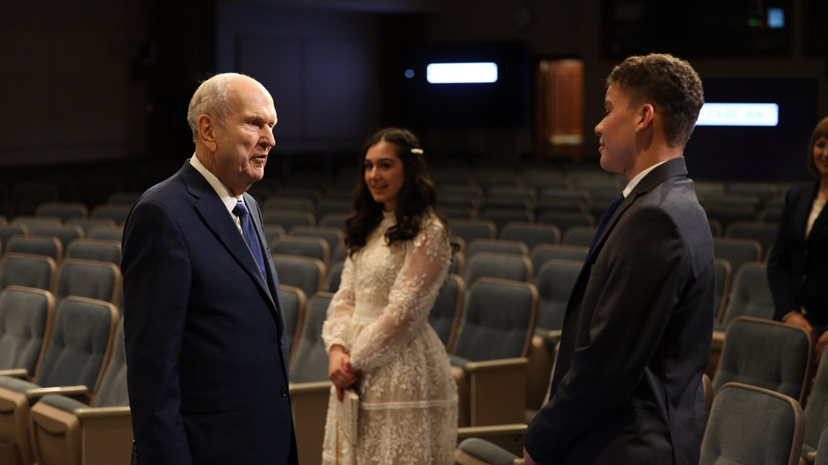 President Russell M. Nelson speaks to youth speakers, Sister Laudy Ruth Kaouk and Brother Enzo Serge Petelo.