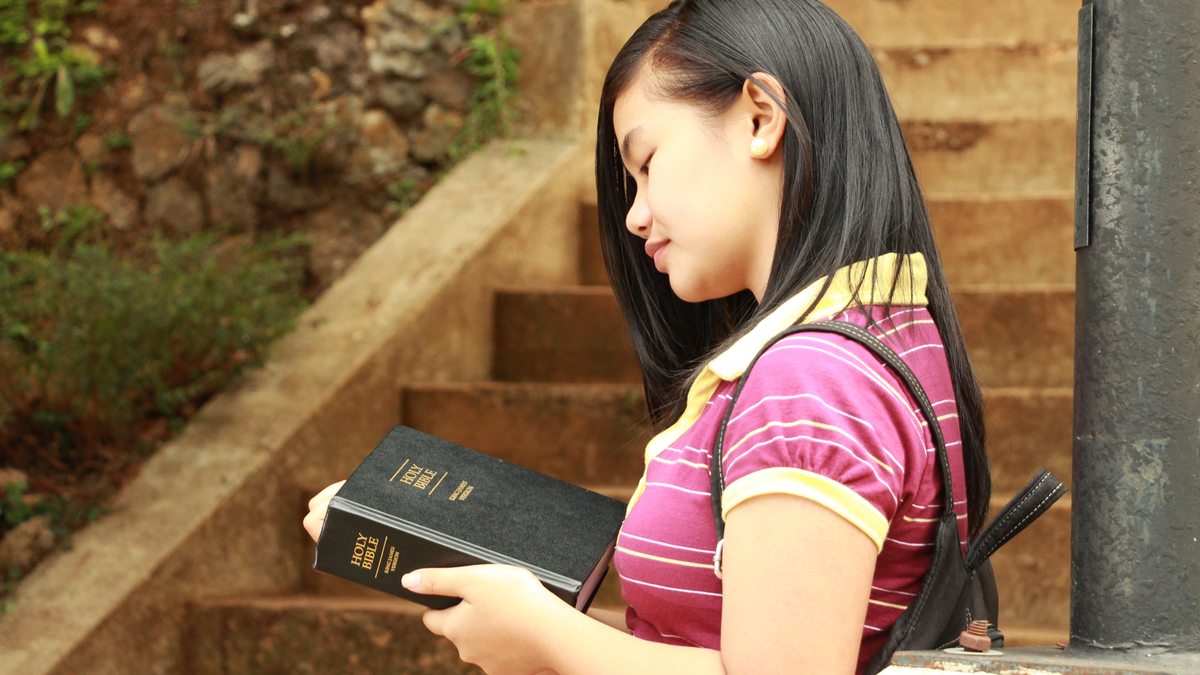 Young woman holding a Bible.
