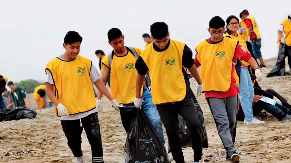 Jóvenes limpiando playa