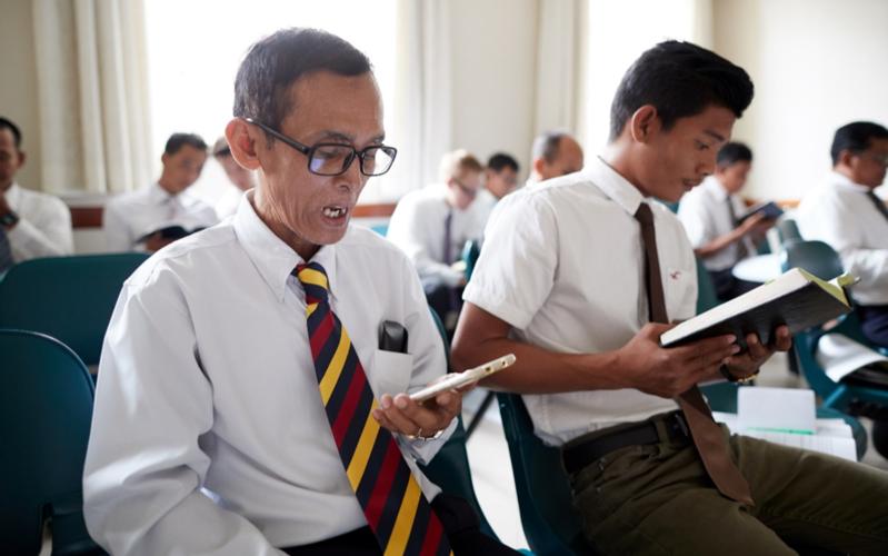 Una clase compuesto de miembros del sacerdocio leyendo las escrituras