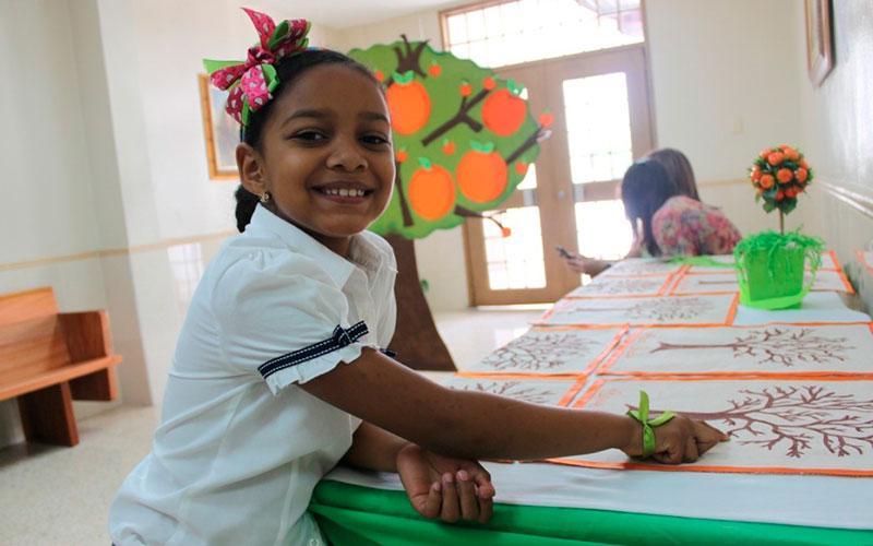 Foto niña junto a su arbol genealógico