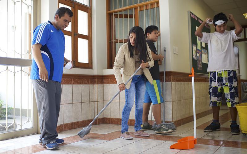 Jóvenes barriendo el piso de la capilla.