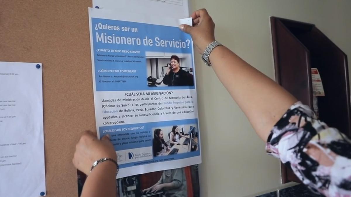 Una misionera SUD colgando un cartel anunciando una actividad.