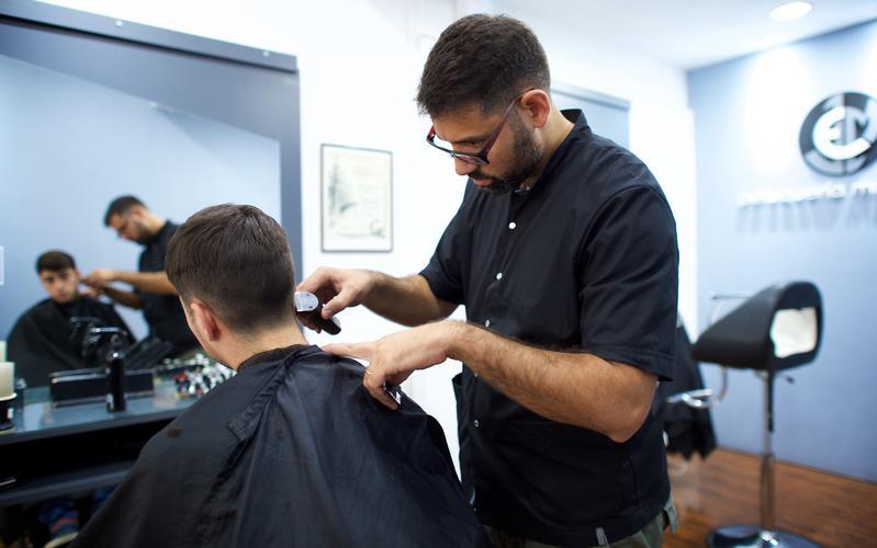 Un peluquero cortando el cabello de un joven.
