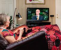 mujer viendo la conferencia mediante la tv
