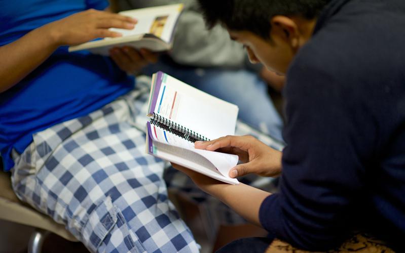 Jóvenes estudiando el evangelio en el libro Predicad Mi Evangelio