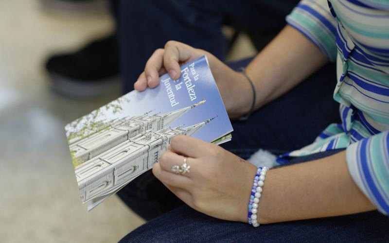 Jóven con el folleto Para la Fortaleza de la Juventud