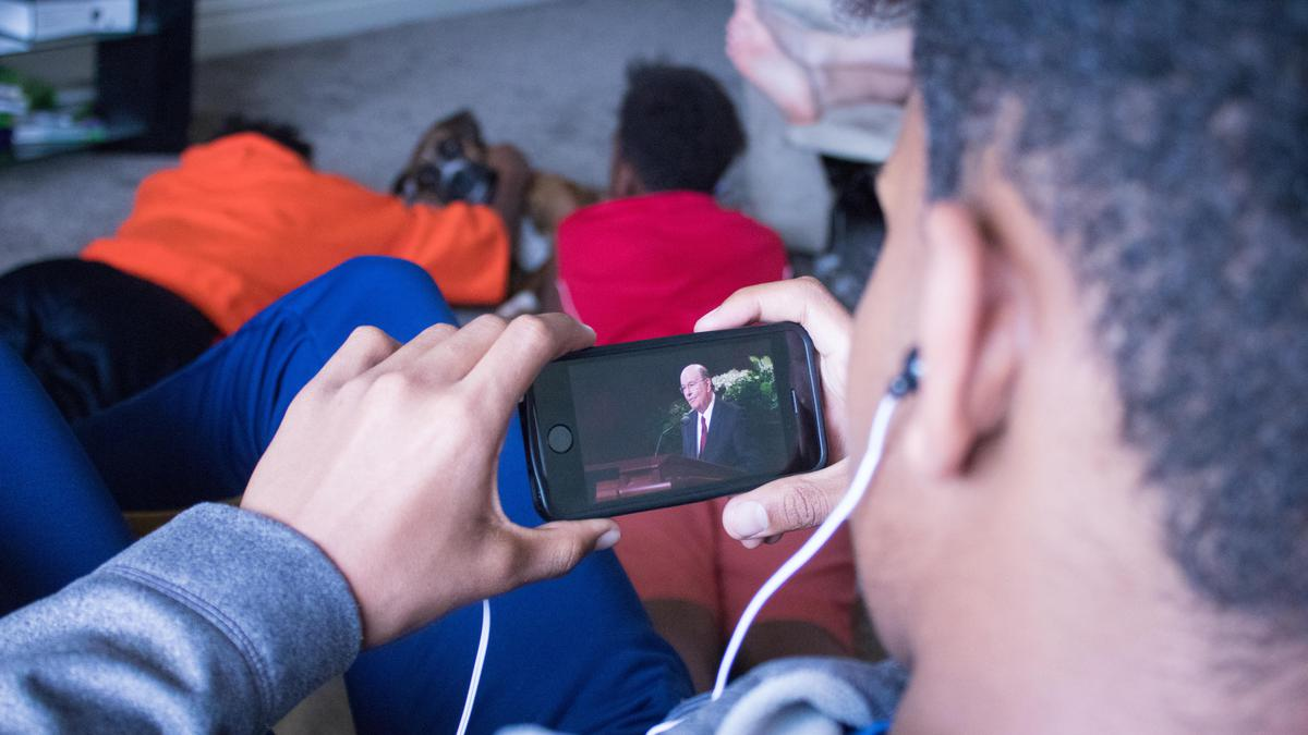 Jovem assistindo à conferência geral no celular