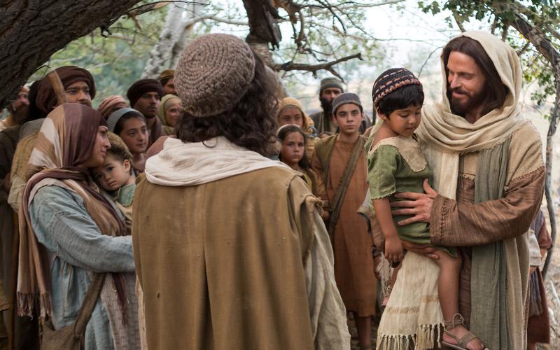 Jesucristo llevando un niño en Sus brazos.
