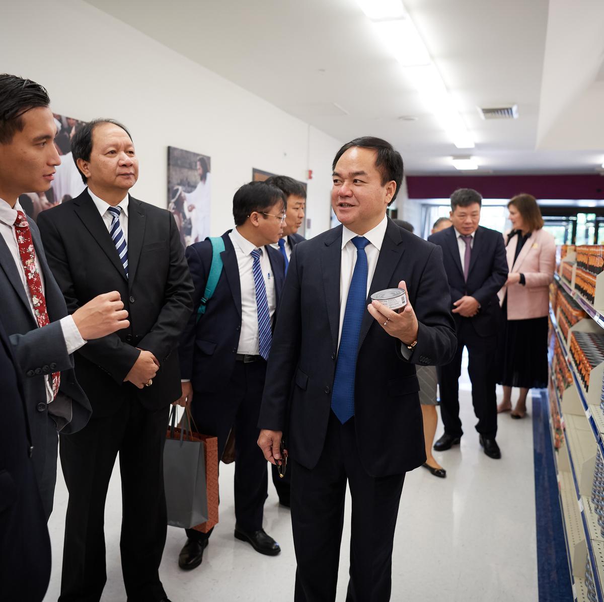นายหวูเจี๊ยนถัง ประธานคณะกรรมการศาสนาของเวียดนาม ถืออาหารกระป๋อง ที่คลังอธิการของศาสนจักร ณ ศูนย์สวัสดิการ ในซอลท์เลคซิตี้