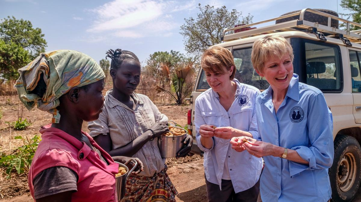 Sister Jean B. Bingham, right, and Sharon Eubank of Latter-day Saint Charities, try local fruits picked by refugee women at Imvepi Refugee Settlement in the Arua district of Uganda. This was part of a a UNICEF field visit to Uganda in early 2017.