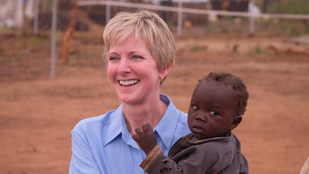 Sister Jean B. Bingham, then serving in the Church's Primary general presidency, carries a boy back to his mother at ECD center in Bid Bidi Refugee Settlement in the Yumbe district of Uganda in early 2017. This was part of a a UNICEF field visit to Uganda.