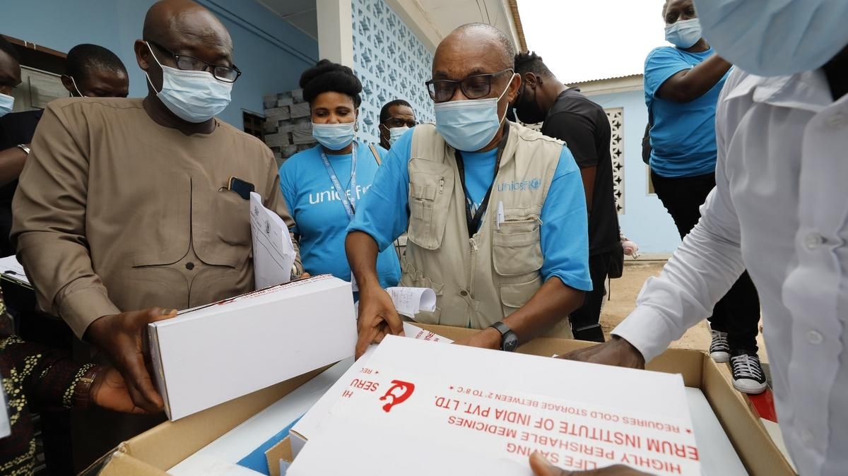 UNICEF staff examine a box containing the first shipment of COVID-19 vaccines distributed by the COVAX Facility in Accra, Ghana, on February 24, 2021.