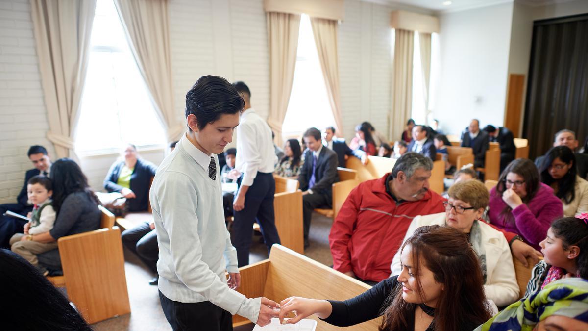 Rapaz distribui o sacramento aos membros da congregação