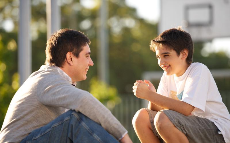 Pai conversando com seu filho sobre gentileza.