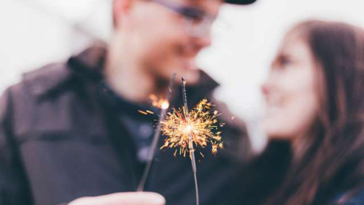 Двойка държи пръчици с бенгалски огън