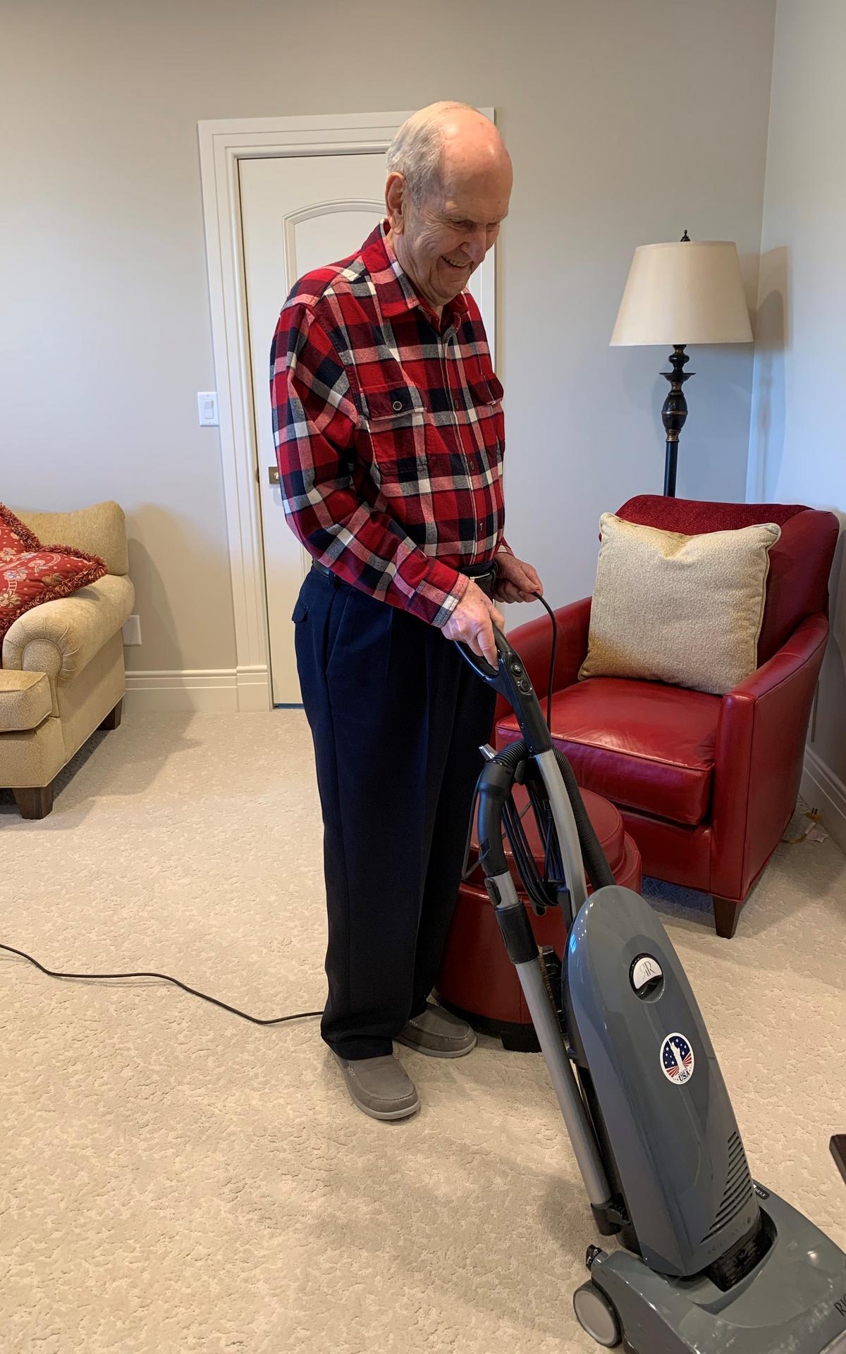 Президент Ръсел М. Нелсън чисти с прахосмукачка