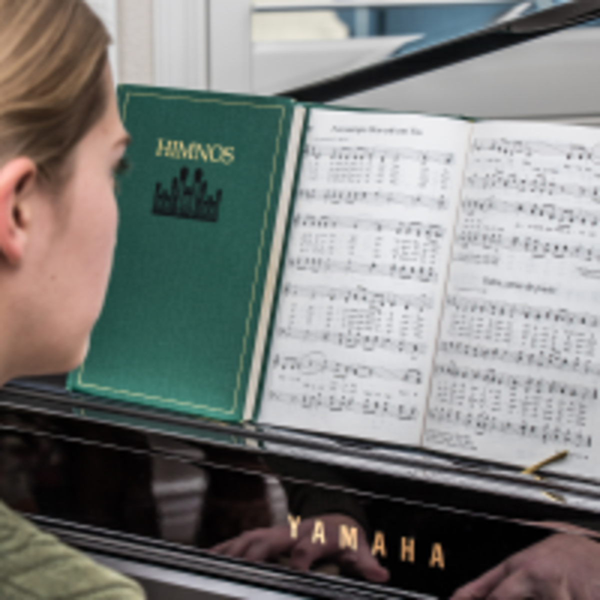 girl playing piano from hymnbook