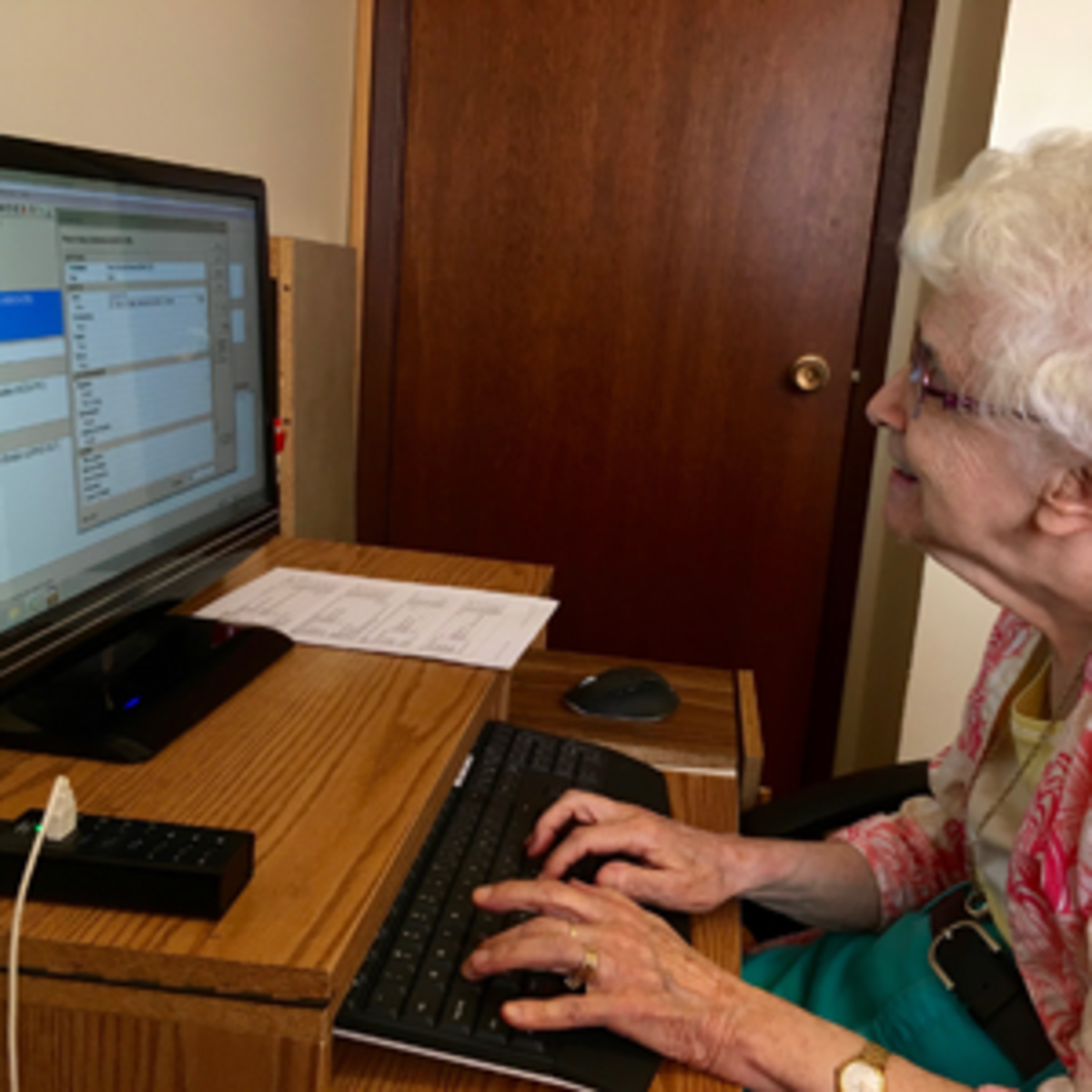 Family History worker at her computer doing research.