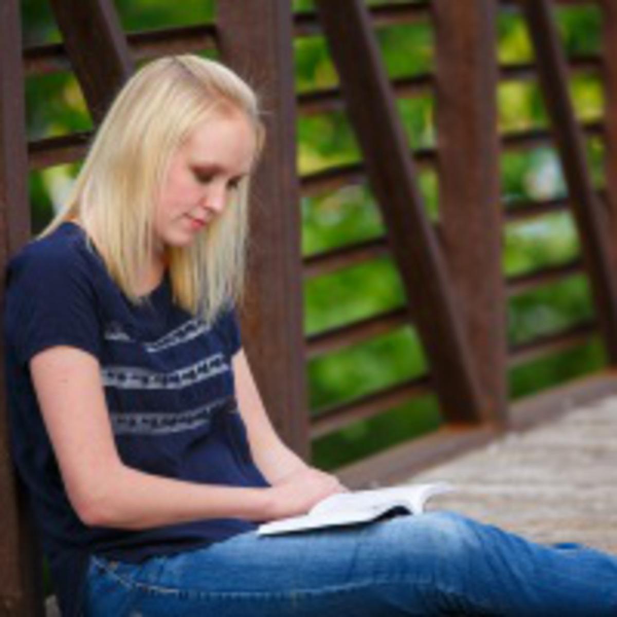 girl reading on bridge