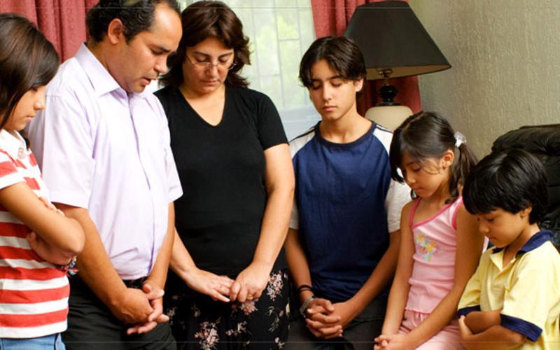 Familia SUD orando juntos.