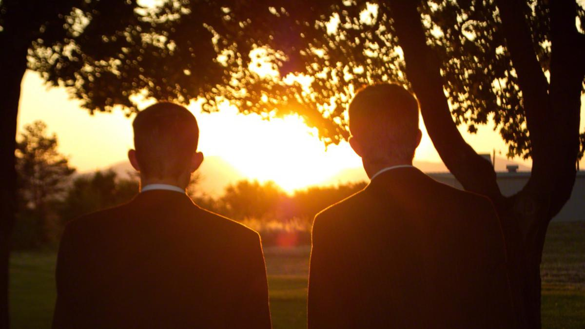 Miembros de la Iglesia de Jesucristo mirando a la puesta del sol.