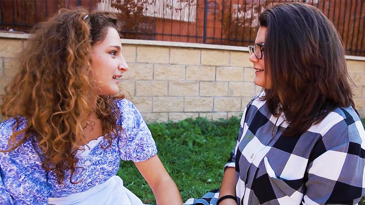 Two girls discussing the gospel together.