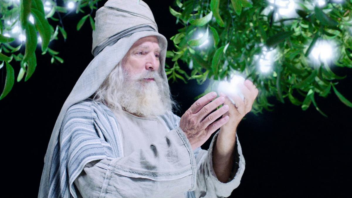 Lehi looking at the glowing white fruit from the tree of life in his hands.