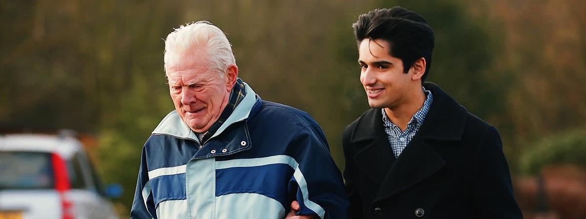 En gammel mand hjælpes over gaden af en yngre mand