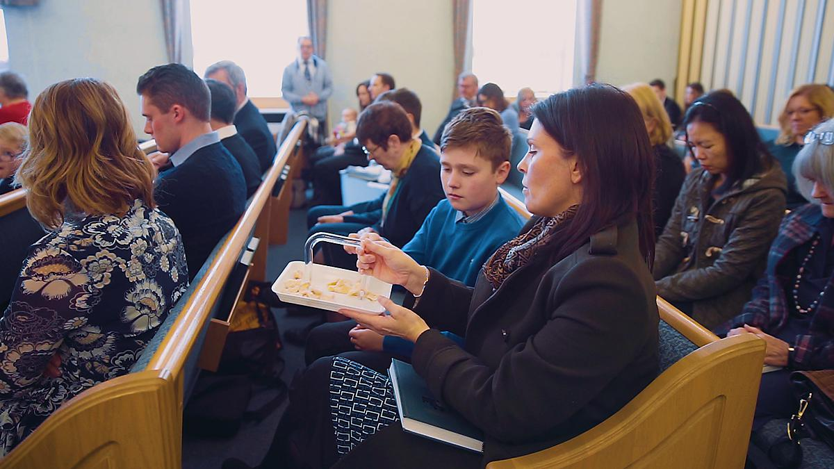 Mother passing sacrament tray to her son.