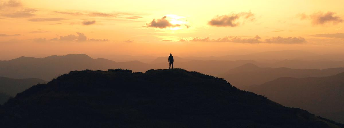 Un hombre en pie, después de alcanzar la cima de una montaña.