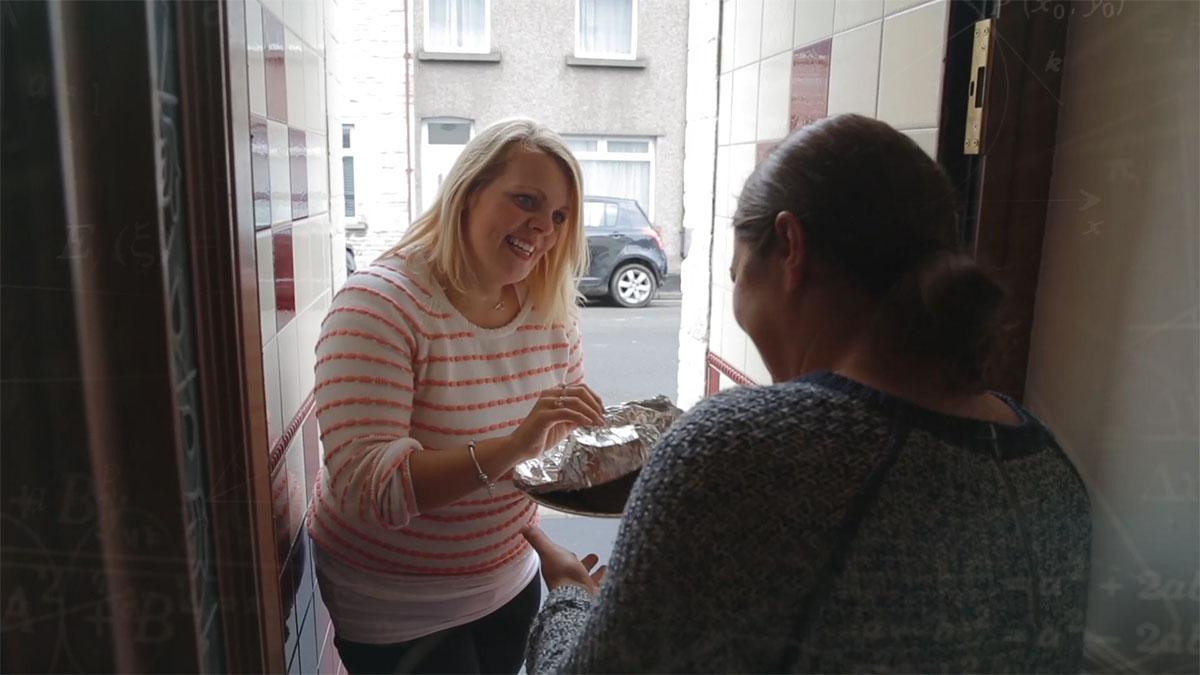 A woman dropping off a plate of food to a neighbour.
