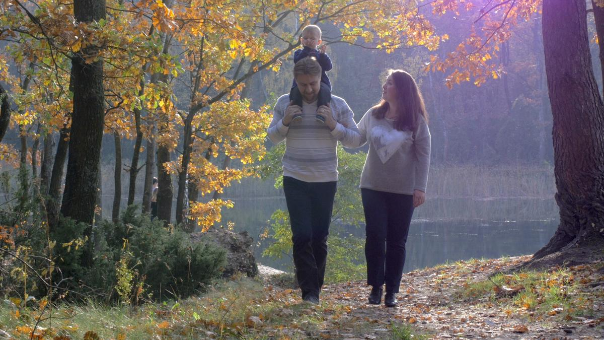 A family walking through a park, smiling