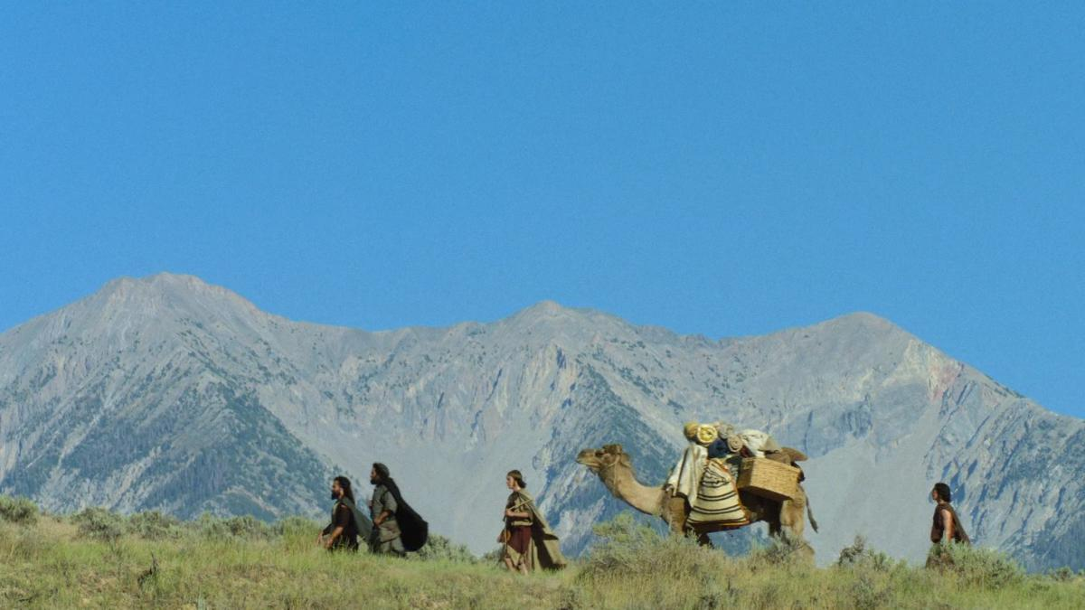 Idúci muži s ťavou, hory a modrá obloha v pozadí