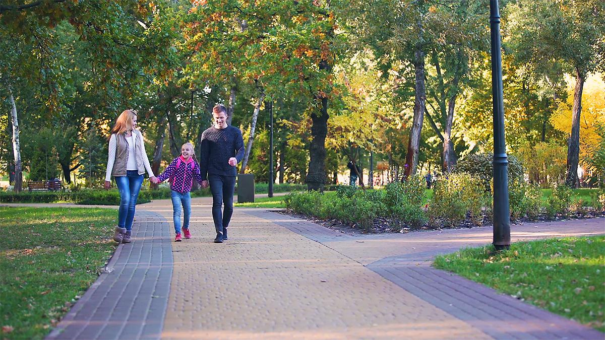 En lykkelig familie går tur sammen i en park.