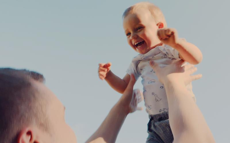 Um pai a lançar o filho ao ar alegremente.