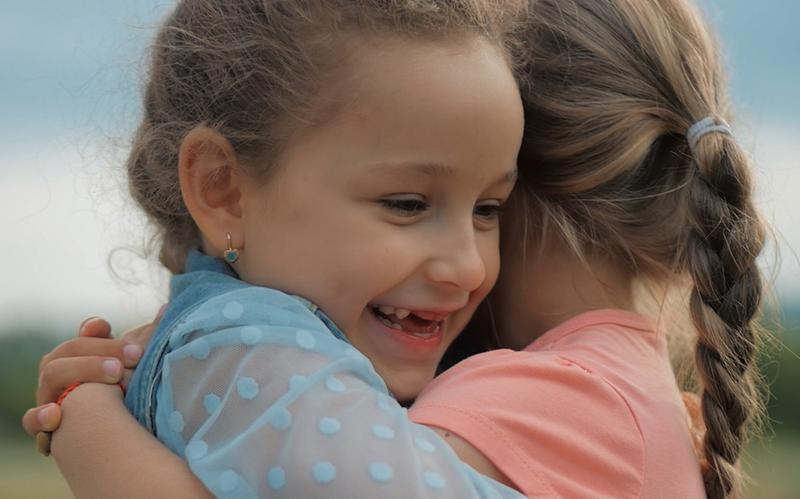 Deux fillettes s'étreignant et se souriant.